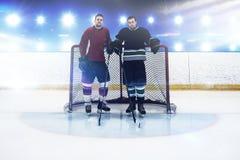 Imagen compuesta de los jugadores del hockey sobre hielo que hacen una pausa el poste de la meta foto de archivo