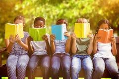 Imagen compuesta de los libros de lectura de los niños en el parque imagen de archivo