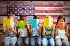 Imagen compuesta de los libros de lectura de los niños en el parque Fotos de archivo libres de regalías