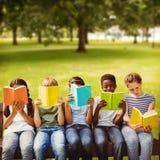 Imagen compuesta de los libros de lectura de los niños en el parque fotografía de archivo
