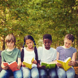 Imagen compuesta de los libros de lectura de los niños en el parque imágenes de archivo libres de regalías
