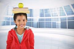 Imagen compuesta de los libros y de la manzana sonrientes de equilibrio de la muchacha en la cabeza imagenes de archivo