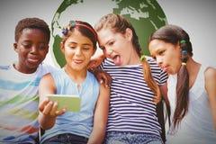 Imagen compuesta de los niños felices que toman el selfie en el parque Fotos de archivo libres de regalías