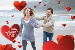 Imagen compuesta de los pares alegres que corren en la playa Foto de archivo libre de regalías