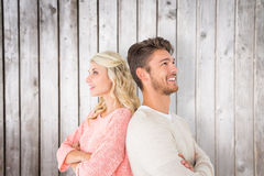 Imagen compuesta de los pares atractivos que sonríen con los brazos cruzados Imagenes de archivo