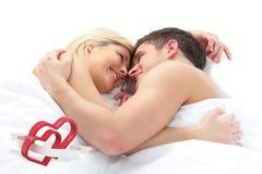 Imagen compuesta de los pares cariñosos que se relajan en cama Foto de archivo