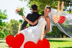 Imagen compuesta de los pares del recién casado que se sientan en la vespa en parque Fotografía de archivo
