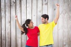 Imagen compuesta de los pares emocionados que animan en camisetas rojas y amarillas Fotos de archivo