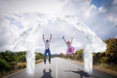 Imagen compuesta de los pares emocionados que saltan en el camino Foto de archivo