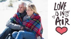 Imagen compuesta de los pares felices envueltos para arriba en la manta que se sienta en la playa Fotografía de archivo