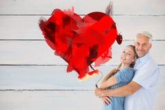 Imagen compuesta de los pares felices que abrazan y que sostienen el rodillo de pintura Imagenes de archivo