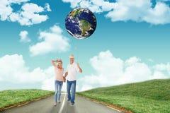 Imagen compuesta de los pares felices que caminan llevando a cabo las manos Imagenes de archivo