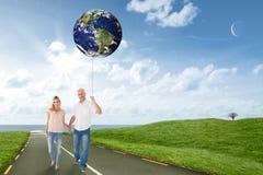 Imagen compuesta de los pares felices que caminan llevando a cabo las manos Imágenes de archivo libres de regalías