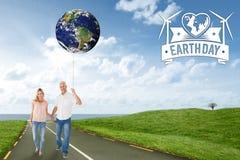 Imagen compuesta de los pares felices que caminan llevando a cabo las manos Fotografía de archivo libre de regalías