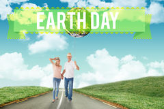 Imagen compuesta de los pares felices que caminan llevando a cabo las manos Imagen de archivo