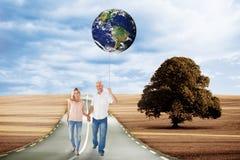 Imagen compuesta de los pares felices que caminan llevando a cabo las manos Foto de archivo libre de regalías