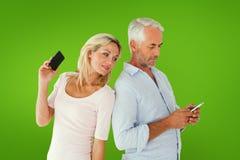 Imagen compuesta de los pares felices que mandan un SMS en sus smartphones fotografía de archivo libre de regalías