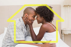 Imagen compuesta de los pares felices que muestran el afecto en cama Fotos de archivo