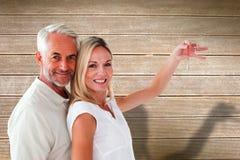 Imagen compuesta de los pares felices que muestran su llave de la nueva casa Imágenes de archivo libres de regalías