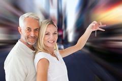 Imagen compuesta de los pares felices que muestran su llave de la nueva casa Imagen de archivo libre de regalías