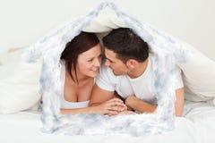 Imagen compuesta de los pares felices que ocultan debajo de una manta Imagenes de archivo