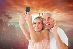 Imagen compuesta de los pares felices que presentan para un selfie Fotos de archivo