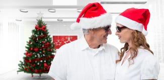 Imagen compuesta de los pares festivos que sonríen en uno a imagen de archivo