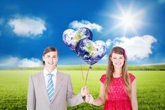 Imagen compuesta de los pares geeky sonrientes que sostienen los globos rojos Imágenes de archivo libres de regalías