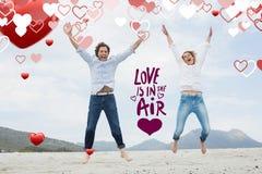 Imagen compuesta de los pares jovenes alegres que saltan en la playa Imagen de archivo