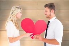 Imagen compuesta de los pares jovenes atractivos que llevan a cabo el corazón rojo Foto de archivo libre de regalías
