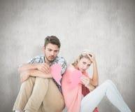 Imagen compuesta de los pares jovenes atractivos que se sientan llevando a cabo dos mitades del corazón quebrado Fotos de archivo