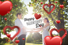 Imagen compuesta de los pares jovenes cariñosos que celebran las manos en el parque Imagen de archivo libre de regalías