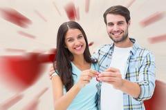 Imagen compuesta de los pares jovenes felices que muestran llave de la nueva casa Fotografía de archivo libre de regalías