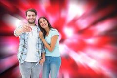 Imagen compuesta de los pares jovenes felices que muestran llave de la nueva casa Imagen de archivo libre de regalías