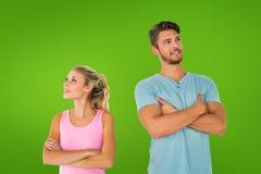 Imagen compuesta de los pares jovenes que presentan con los brazos cruzados Imagen de archivo libre de regalías
