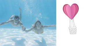 Imagen compuesta de los pares lindos que sonríen en la cámara bajo el agua en la piscina Foto de archivo libre de regalías