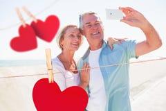 Imagen compuesta de los pares mayores felices que presentan para un selfie Fotografía de archivo
