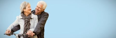 Imagen compuesta de los pares mayores que se sientan en la bicicleta mientras que sonríe imagen de archivo libre de regalías