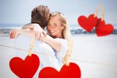 Imagen compuesta de los pares que abrazan en la playa Fotos de archivo libres de regalías
