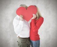 Imagen compuesta de los pares que abrazan y que llevan a cabo el corazón sobre caras Imagenes de archivo