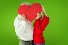 Imagen compuesta de los pares que abrazan y que llevan a cabo el corazón sobre caras Imágenes de archivo libres de regalías