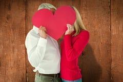 Imagen compuesta de los pares que abrazan y que llevan a cabo el corazón sobre caras Foto de archivo libre de regalías