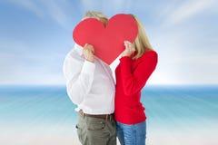 Imagen compuesta de los pares que abrazan y que llevan a cabo el corazón sobre caras Fotos de archivo libres de regalías