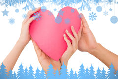 Imagen compuesta de los pares que llevan a cabo un corazón de papel Foto de archivo libre de regalías