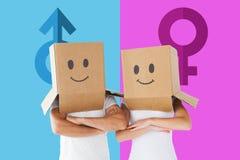 Imagen compuesta de los pares que llevan las cajas sonrientes de la cara en sus cabezas Imagenes de archivo
