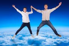 Imagen compuesta de los pares que saltan y que llevan a cabo las manos Imágenes de archivo libres de regalías