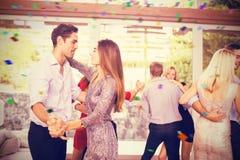 Imagen compuesta de los pares que se abrazan mientras que baila Fotografía de archivo