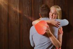 Imagen compuesta de los pares que se abrazan mientras que sostiene el regalo Fotografía de archivo libre de regalías