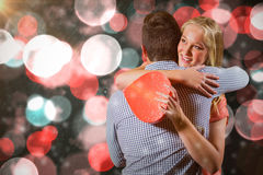 Imagen compuesta de los pares que se abrazan mientras que sostiene el regalo Fotos de archivo