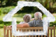 Imagen compuesta de los pares que se sientan en el banco con su de nuevo a la cámara Fotografía de archivo